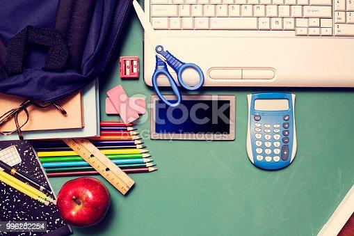 istock Laptop, school supplies on green chalkboard in knolling arrangement. 996252254