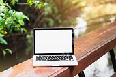 istock Laptop screen is blank are placed on a wooden table and trees with nature that are beautiful on a light rainy day. 1283286541