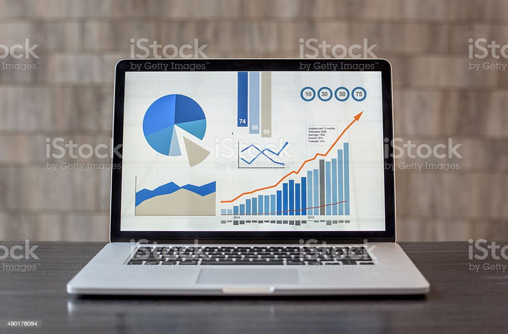 Laptop showing business graphs at the office stock photo
