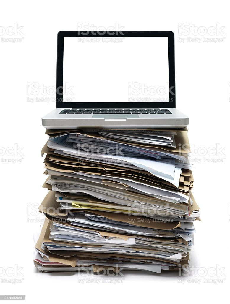 Laptop sitting on a mound of paperwork stock photo
