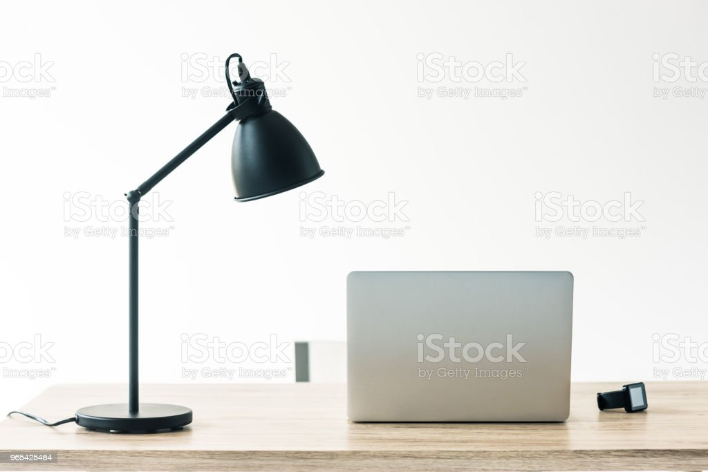 laptop, smartwatch and lamp on wooden table in office zbiór zdjęć royalty-free