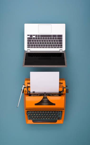 laptop vs retro typewriter stock photo