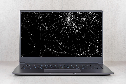 laptop with a broken screen in cracks on a gray background close up front view
