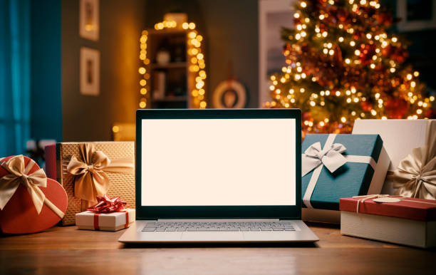 Laptop with blank screen and Christmas gifts stock photo