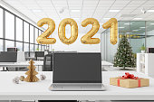 istock Laptop With Blank Screen In An Office Decorated With Christmas Tree 1267081182