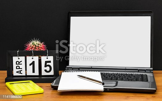 istock Laptop with blank screen, office supplies and date of 15 april at the workplace. Front view. Tax day concept. 1141586650