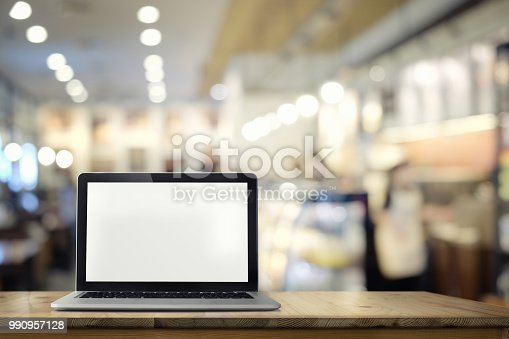 Laptop with blank screen on wooden table with blur cafe, restaurant backgrounds.