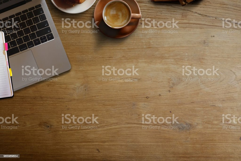Laptop with brown coffee cup and copy space on the wooden desk table. - Royalty-free Above Stock Photo