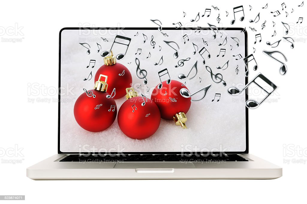 Laptop with Christmas balls and many flying musical note stock photo