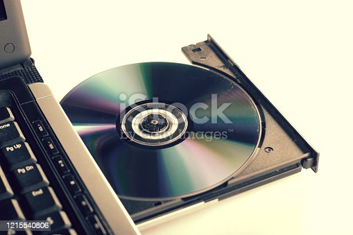 Laptop with dvd drive open and loaded and a pile of dvd