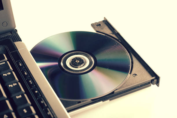 Laptop with dvd drive open and loaded and a pile of dvd stock photo