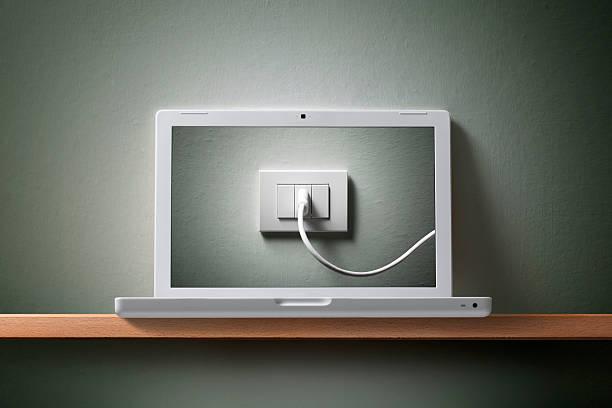 ordinateur portable avec le câble électrique dans la multiprise. - prise électrique à trois fiches photos et images de collection