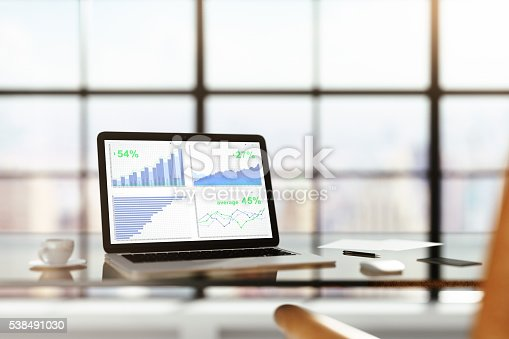 istock Laptop with financial statistics on a glass table with cup 538491030