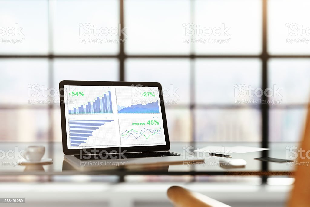 Laptop with financial statistics on a glass table with cup stock photo