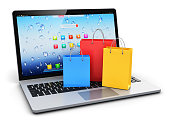 istock Laptop with group of color paper shopping bags 655499528