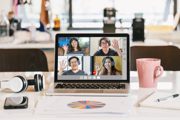 laptop with headphone, coffee cup, mobile phone and data graph document showing Asian Business people say hello with teamwork colleague in video conference