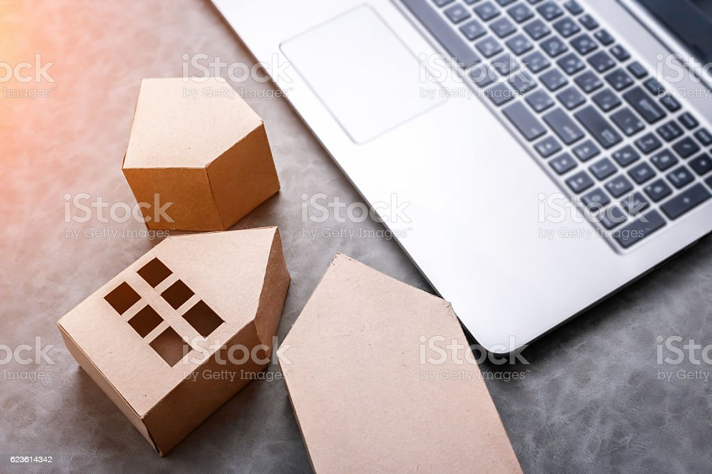 laptop with house in brown recycled paper stock photo