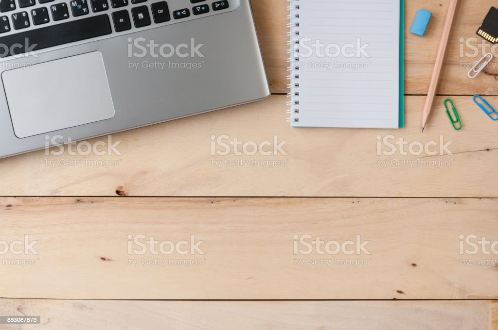 Laptop with notebook, paper clips  and pencil on wooden table, top view shot stock photo