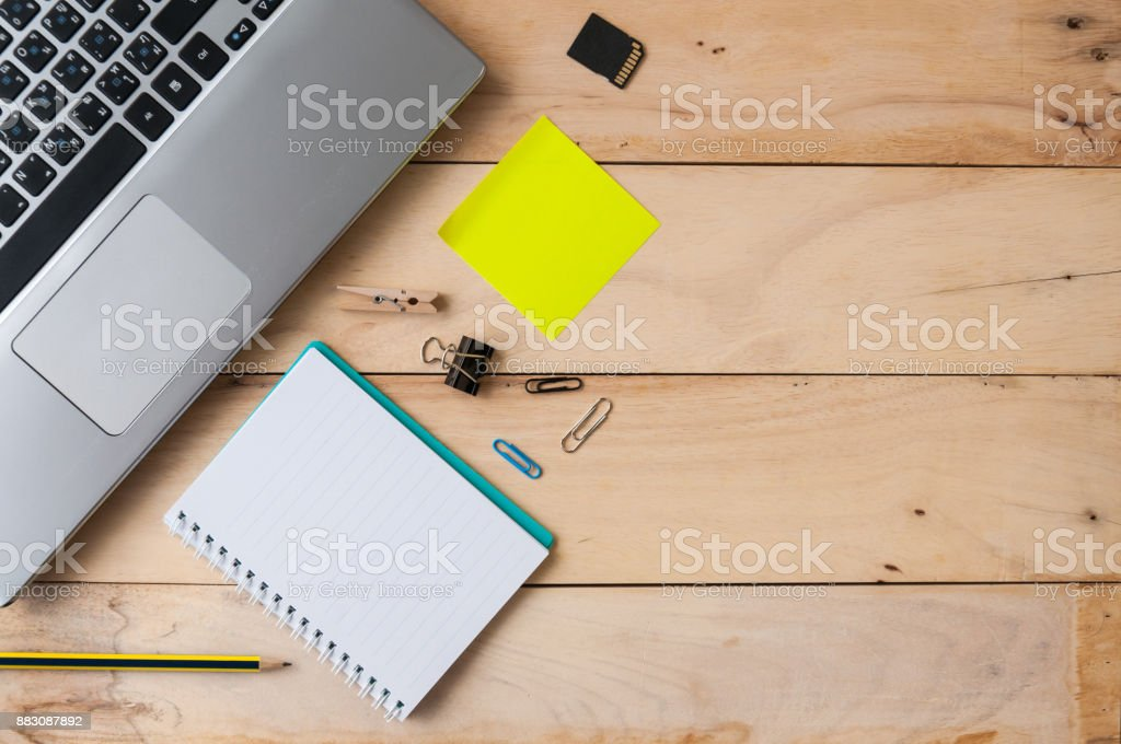 Laptop with notebook, paper clips, notepad and pencil on wooden table, top view shot stock photo
