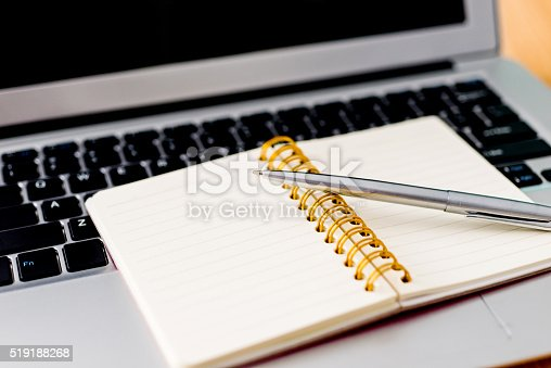 519189026 istock photo Laptop with pen and spiral notebook 519188268