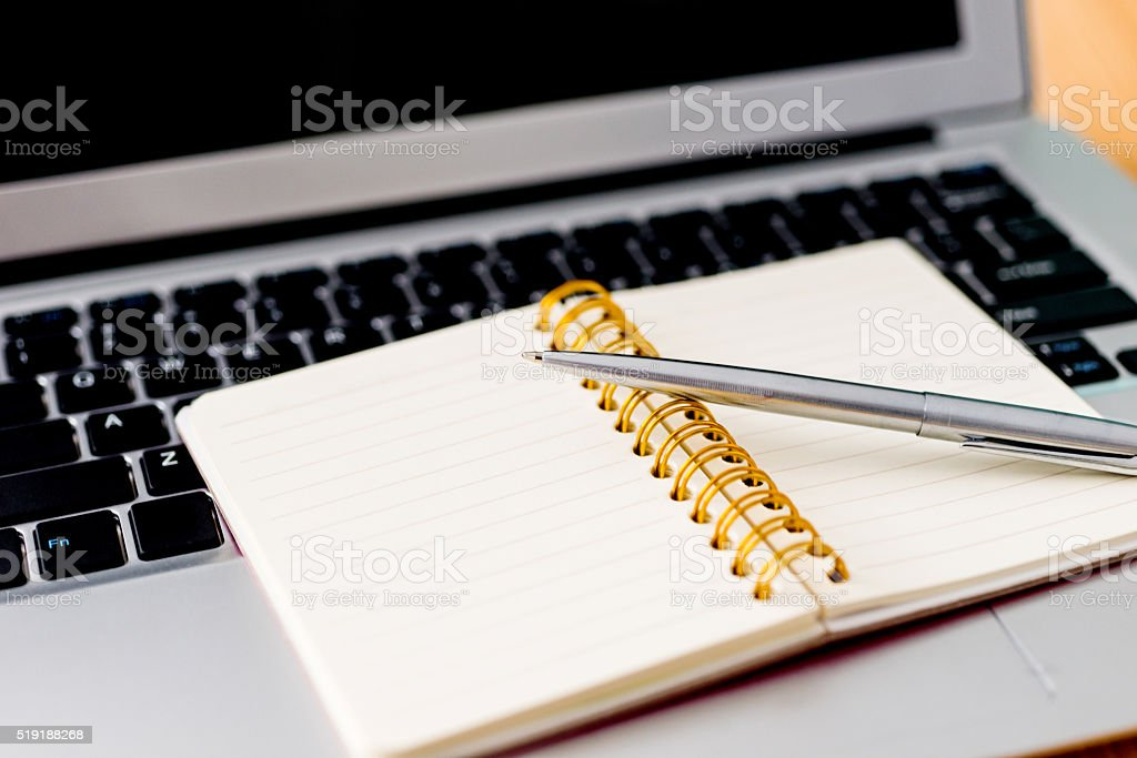 Laptop with pen and spiral notebook stock photo
