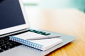 Laptop with pen and spiral notebook