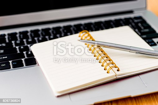 519189026 istock photo Laptop with pen and spiral notebook 826736804