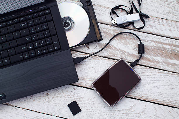 Laptop with pendrive, sd card, CD and portable hard drive. stock photo