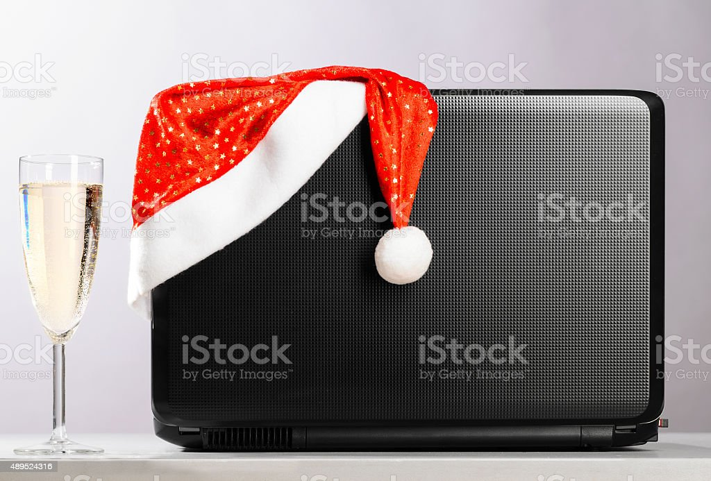 laptop with santa hat and wine stock photo