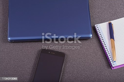 1173922060 istock photo laptop with smartphone and notebook to take notes 1134310065