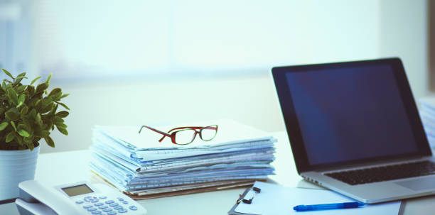 Laptop with stack of folders on table on white background – zdjęcie