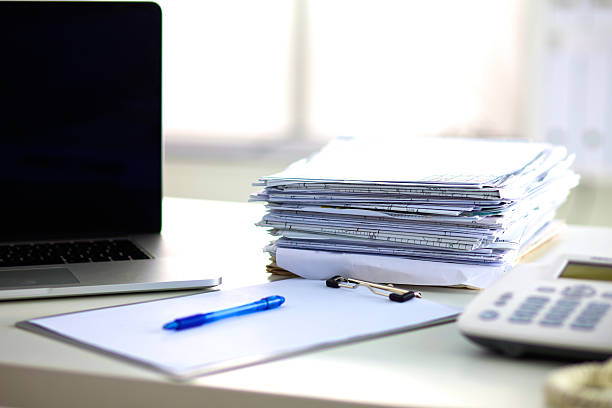 Laptop with stack of folders on table  white background – zdjęcie