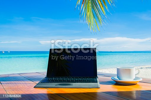 istock Laptops under palm tree on tropical beache 1124646304