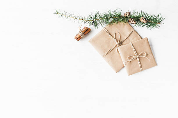 larch branches, cinnamon sticks, christmas gift. flat lay, top view - handgemachte geschenke stock-fotos und bilder