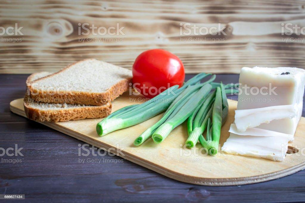 Schmalz (Salo), grüne Zwiebeln, Brot, rote Tomaten auf einem hölzernen Hintergrund. Lizenzfreies stock-foto