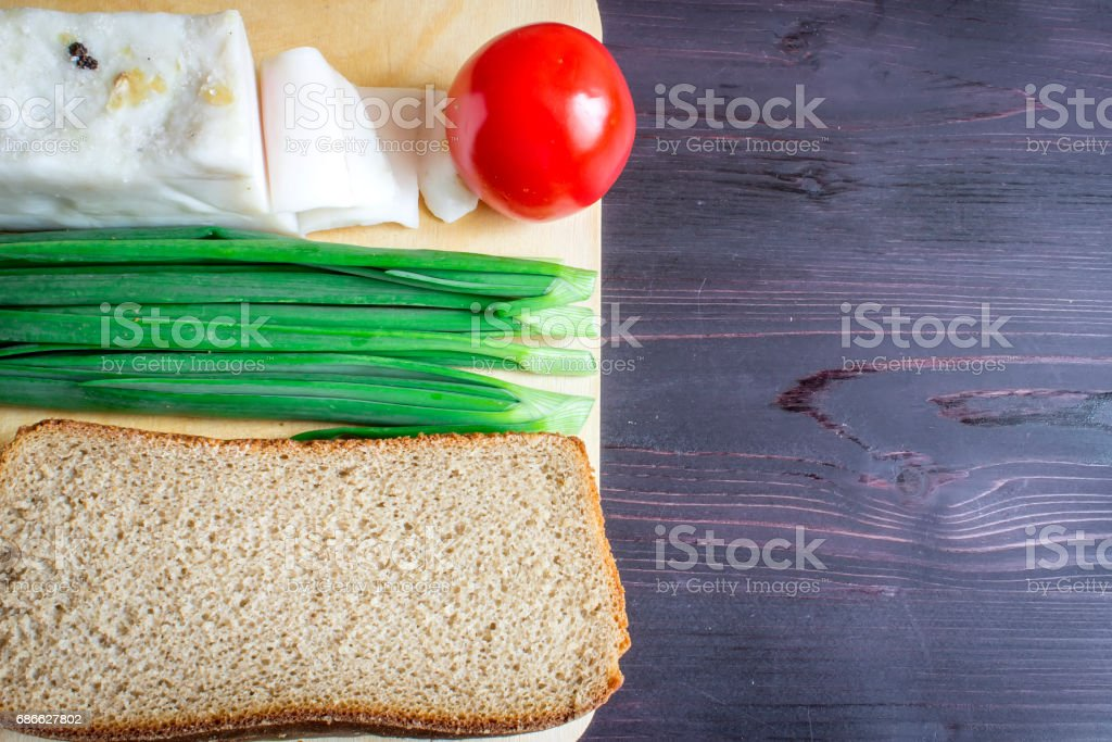 Lard (Salo), green onions, bread, red tomato on a wooden background. royalty-free stock photo