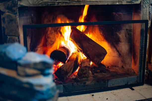 Lareira acesa com lenha queimando Devido as baixas temperaturas é muito prazeroso acender uma lareira e tomar uma bebida alcóolica para aquecer o corpo. Equipamentos de lareira, tais como pá para tirar carvão, vassoura e espeto para apanhar lenha. log fire stock pictures, royalty-free photos & images