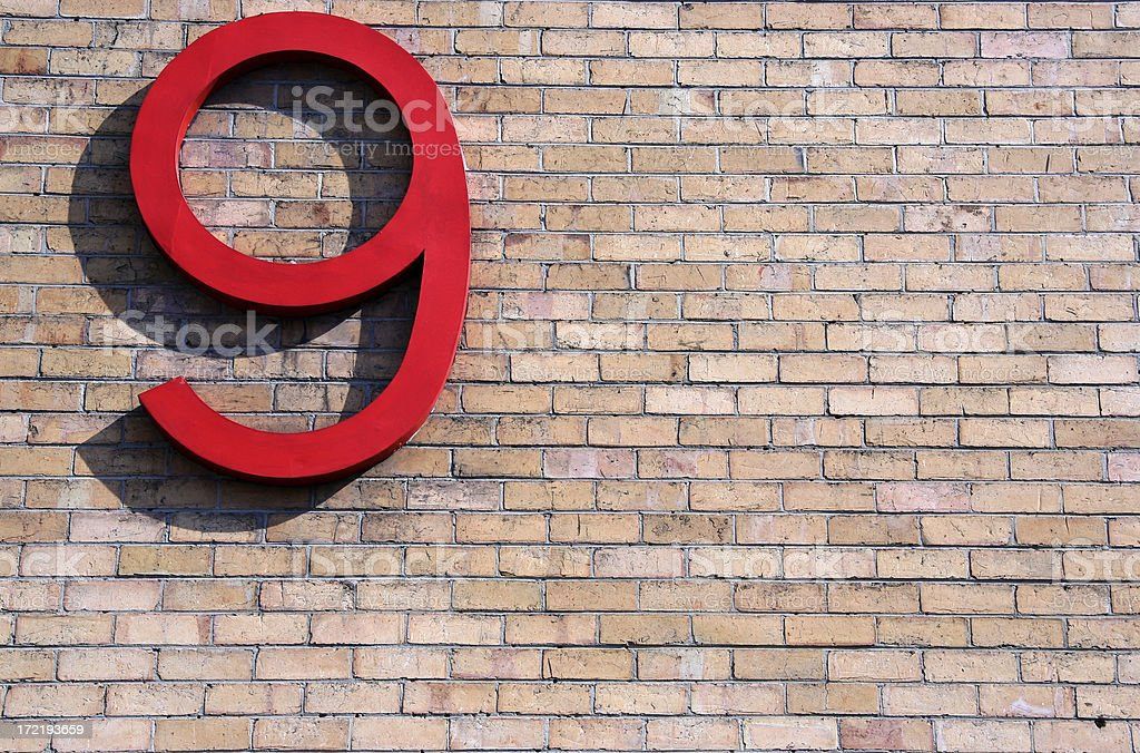 Large 3D red nine symbol in sunlight on brick wall royalty-free stock photo
