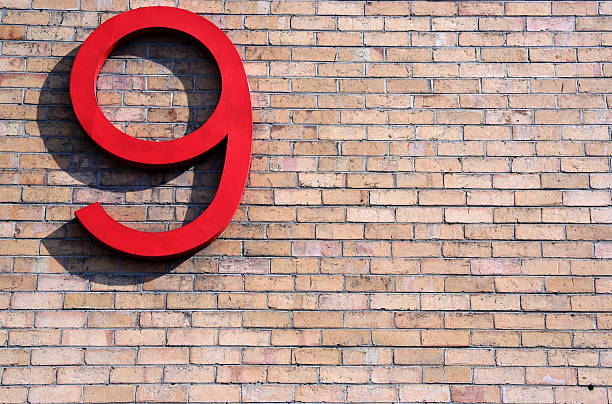 Large 3D red nine symbol in sunlight on brick wall stock photo