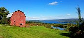 Sunlit vintage red barn on a hillside with lake waters in the distance; bright colors of green, blue and red.