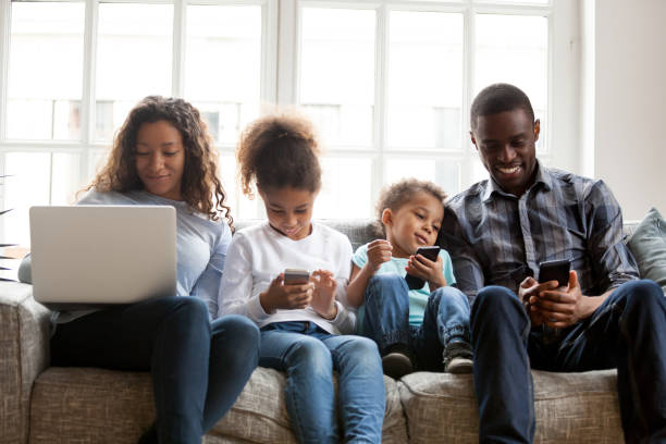 Large African American family using devices, sitting together stock photo