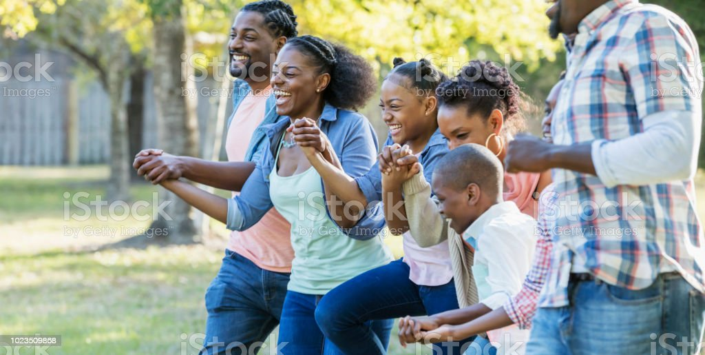 Large African-American family running together at park stock photo