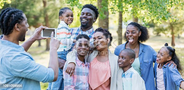1091098220istockphoto Large African-American family, taking photo with phone 1091099954