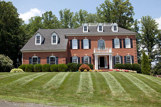 Large American Home Large new American House in red brick with lovely green lawn in summer colonial style stock pictures, royalty-free photos & images
