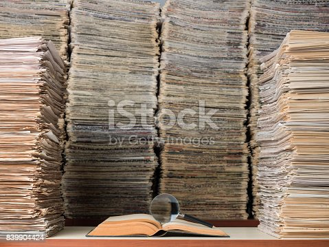 View of large amount of documents, newspapers, and books in classic library. A magnifying glass seen on top of an open book on desk. No people are seen in frame. Shot with a medium format camera.