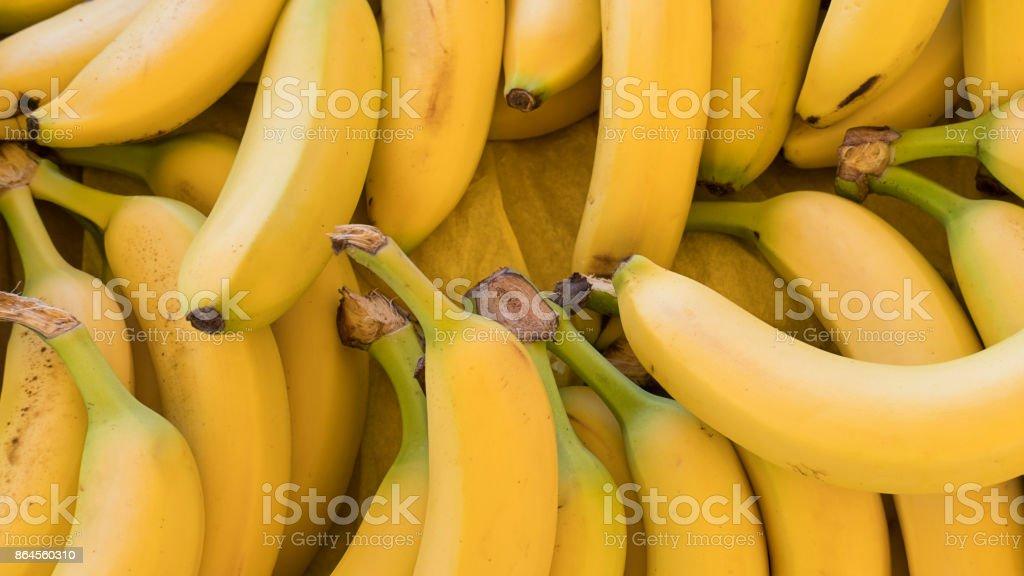 Una gran cantidad de maduros y sanos buscando plátanos en el mercado bajo la luz del sol de mediodía - foto de stock