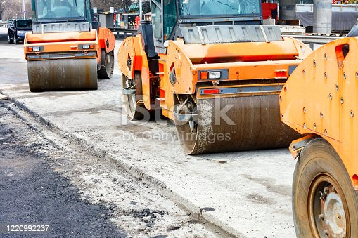 A number of heavy orange vibratory rollers are parked at the edge of a new work area awaiting work during the construction of a new traffic intersection.
