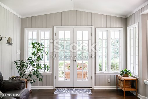Large and open living room den sun room with windows on two sides and lots of natural light flowing in. There is a window seat on one side and a leather couch and plant on the other.