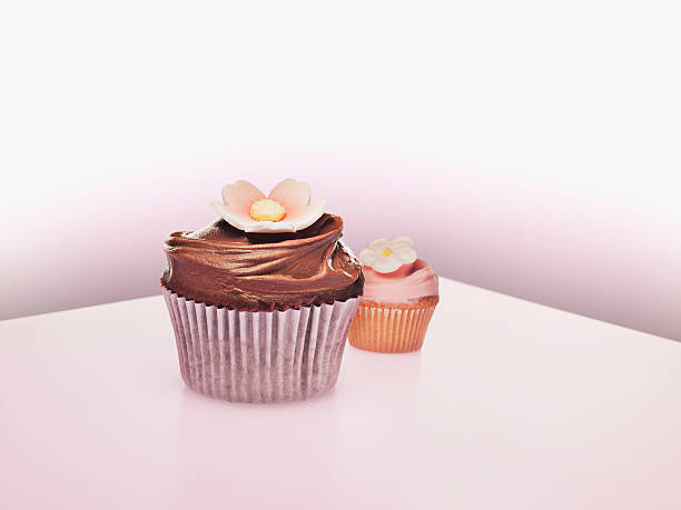 large and small cupcakes with flower decorations - big cake stock photos and pictures
