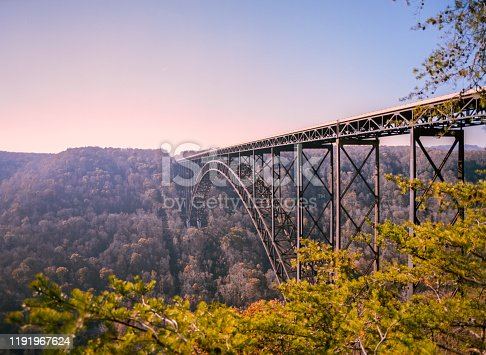 Iron and Steel Bridge over a wide deep gorge with trees in the foreground.